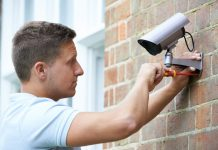 man installing best outdoor wireless security camera system with dvr