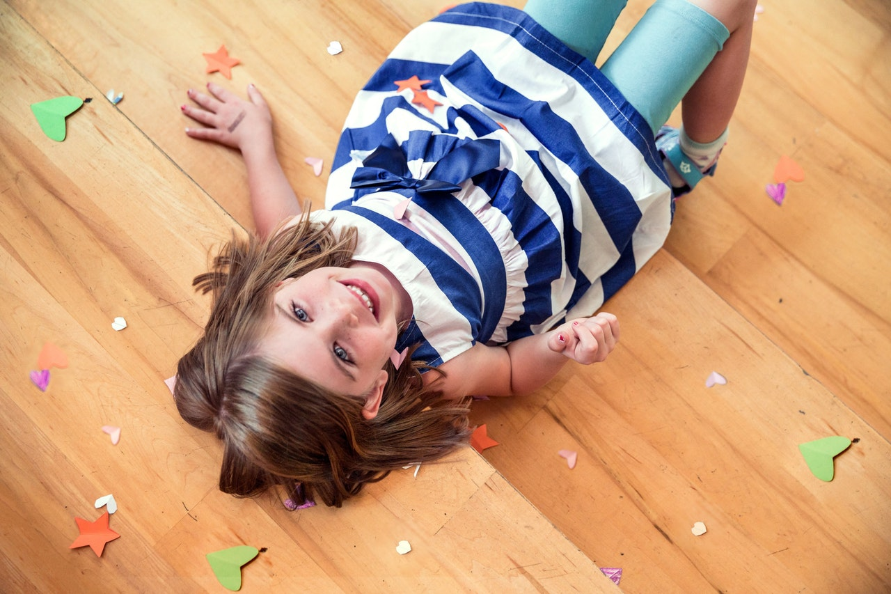 child lying down on a hardwood floor which is  one of the best types of flooring
