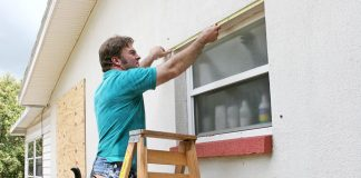 man in blue shirt putting screen on window
