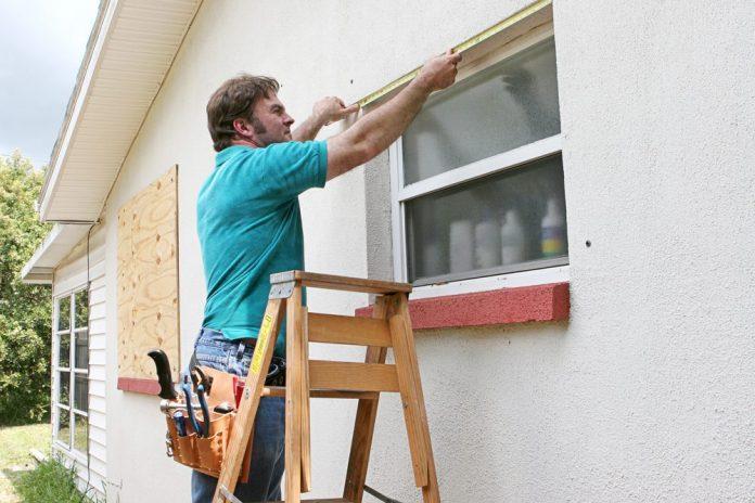 man in blue shirt putting screen on window